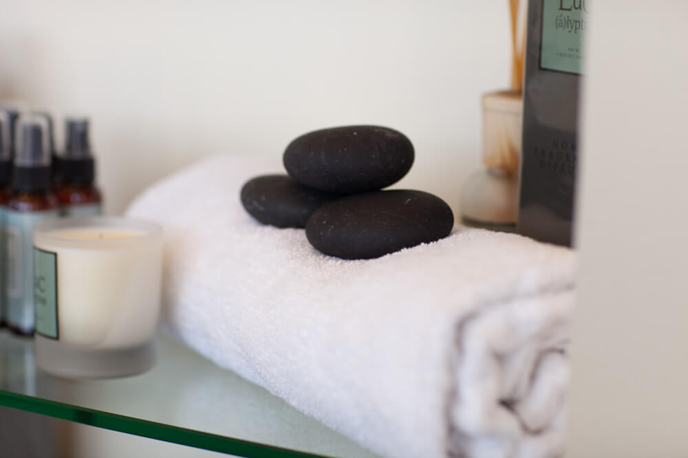 Towel, hot stones and candle on shelf